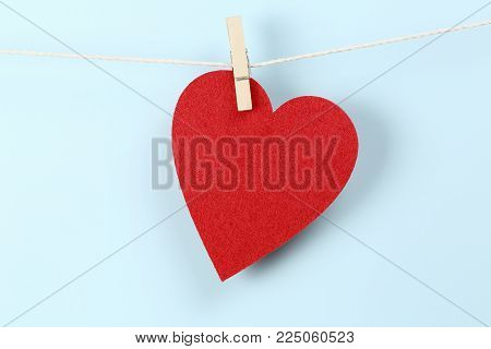 red felt heart caught on clothesline with peg