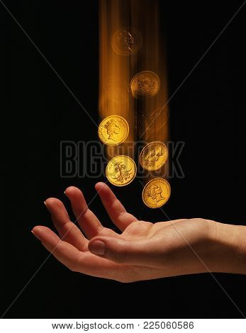 Pound Coins Falling Into Girls Hand On Black Background