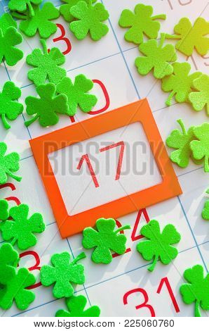 St Patrick's Day festive card. Green quatrefoils on the calendar with orange framed 17 March - St Patrick's day holiday date. Festive postcard for St Patrick's holiday