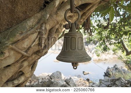The brass bell hanging on the tree above the Hindu altar in the woods. The altar near the river, far from the village, where one can stop and pray