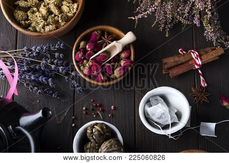 Different herbs for making healthy tea on dark bacground with different tea and dried flowers, flat lay