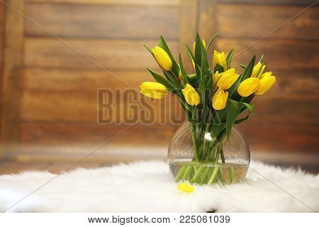 A bouquet of yellow tulips in a vase on the floor. A gift to a woman's day from yellow tulip flowers. Beautiful yellow flowers in vase by wall.
