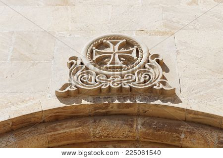 Maltese cross on the wall of the building bas-relief