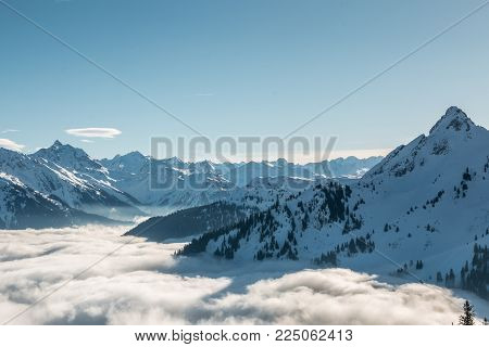 Snow on the top of the mountains and fog down the valley