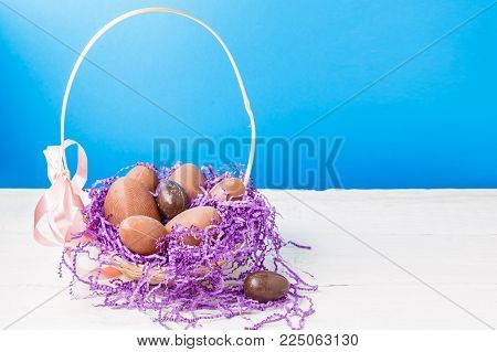 chocolate eggs, purple decorative paper in basket on empty blue background