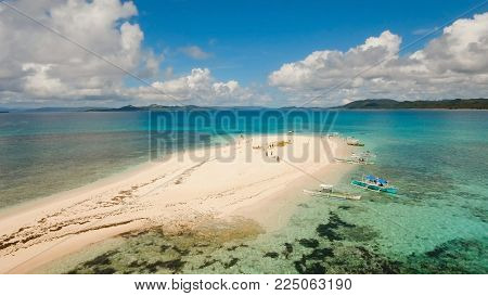Aerial view of beautiful sand tropical island with white sand beach and tourists. White sand island. Seascape: ocean and beautiful beach paradise. Philippines, Siargao. Travel concept.