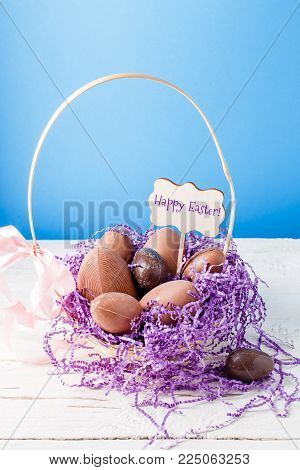 chocolate eggs, purple decorative paper in basket on empty blue background with wish for happy Easter