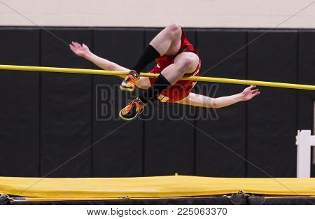 A high school high jumper competing in a track and field event attempeting to clear the bar.