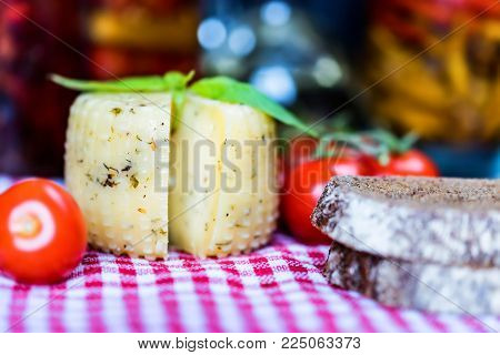 Close up rustic cheesehead with herbs, rye bread and tomatoes on checkered tablecloth, selective focus