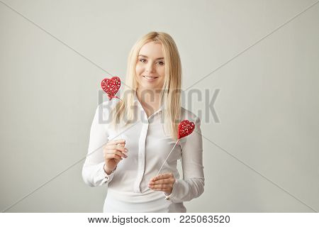 Surprised beauty young girl fashion model with Valentine hearts in the hand. Love. Valentine's day gift. Isolated on a light background.