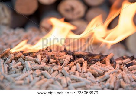 Wooden pellets in flames - wooden biomass, renewable energy