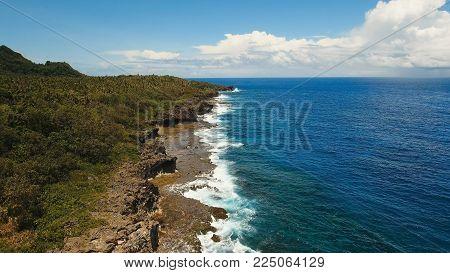 Rocky coast line of Island Siargao. Aerial view sea rocky coast, waves breaking to the rocky shore. Sea landscape, rocks, waves breaking about the shore. Rocky coastline. Philippines. Travel concept.