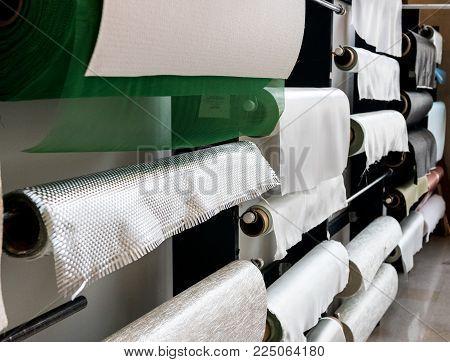 Fiberglass composite fabrics hanging on a wall dispenser