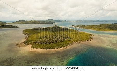 Aerial view: beach, tropical island, sea bay and lagoon, Siargao. Tropical landscape hill, clouds and mountains rocks with rainforest. Azure water of lagoon. Shore Landscape Bay. Seascape. Travel concept.