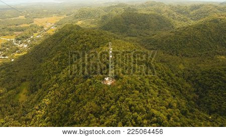 Communication tower, cellphone tower in the jungle in the mountains. Aerial view: satellite, cellphone tower, on a mountain. View of a tropical island with palm trees and other vegetation, a mountain and white telecom radio tower.