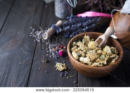 Different herbs for making healthy tea, cinnamon, dried rose in bowl, camomile flowers on wooden background top view, copy space, horizontal composition