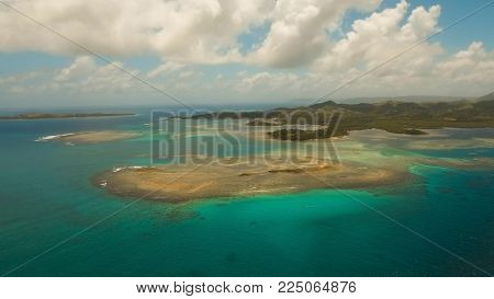 Aerial view: beach, tropical island, sea bay and lagoon, Siargao. Tropical landscape hill, clouds and mountains rocks with rainforest. Azure water of lagoon. Shore Landscape Bay. Aerial video.Seascape.