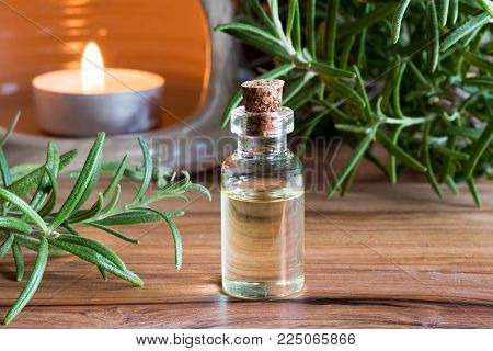 A bottle of rosemary essential oil with fresh rosemary twigs and a candle in the background