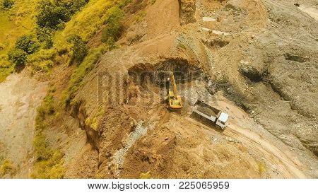 Excavator loads the truck in quarry. Aerial view wheel loader excavator machine loading dumper truck at quarry. Earth mover loading dumper truck with rocks in quarry. Philippines. Travel concept.
