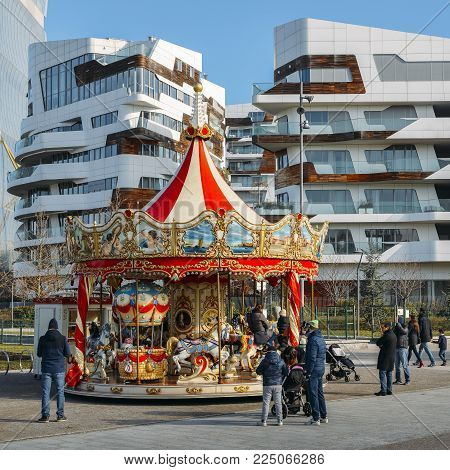 Milan, Italy - Feb 4, 2018: Kids and family play in a merry-go-round set up in the Tre Torri Citylife district of Milan, Italy during a sunny winter day