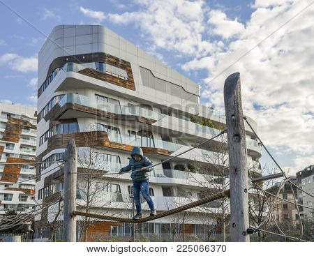 Milan, Italy - Feb 4, 2018: Small boy aged 4-6 plays on a tight rope set up in a playground in the Tre Torri Citylife distrct of Milan, Italy during a sunny winter day