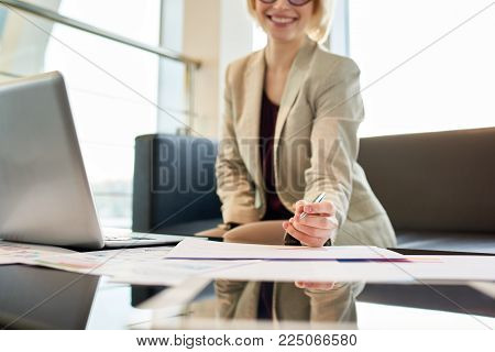 Cheerful young entrepreneur in formalwear taking necessary notes while preparing for important negotiations with business partner, office interior on background