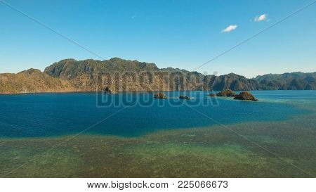 Aerial view: beach, tropical island, sea bay and lagoon, mountains with rainforest, Palawan. Lagoon with blue, azure water in the middle of small islands and rocks. Busuanga. Seascape, tropical landscape. Philippines. Travel concept