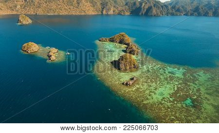 Aerial view: beach, tropical island, sea bay and lagoon, Palawan. Lagoon with blue, azure water in the middle of small islands and rocks. Busuanga. Seascape, tropical landscape. Philippines.