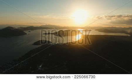Sunset Sunset over a tropical bay. Aerial view: Sunset over the sea in the background orange sky. Fly over the ocean in sunset time. Travel concept. Nothing but sky, clouds and water. Beautiful serene scene. Philippines, Siargao.