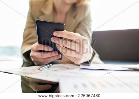 Close-up shot of unrecognizable white collar worker sitting at coffee table of office lobby and browsing Internet on smartphone, blurred background