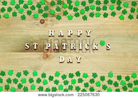 St Patrick's day card. St Patrick's Day background. Green quatrefoils on the wooden background and wooden inscription Happy St Patrick's day. Festive St Patrick's day background