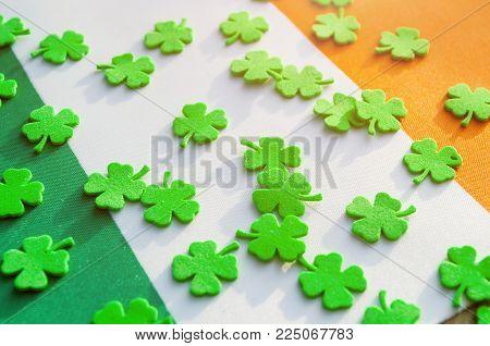 Irish flag and quatrefoils, St Patrick's day concept. St Patrick's Day festive background. Green quatrefoils above the Irish national flag, St Patrick's day holiday concept, St Patrick's day still life