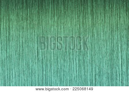 The texture is green ribbed and rough tile. Background of ceramic tiles with thin vertical stripes. Striped background of sheet metal or ceramic floor tiles.