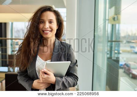 Waist-up portrait of attractive young businesswoman in formalwear posing for photography with charming smile while holding digital tablet in hands, interior of spacious office lobby on background