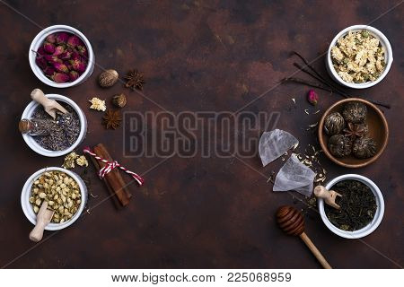 Different herbs for making healthy tea, cinnamon, dried rose , camomile flowers on stone background, top view, copy space, horizontal composition