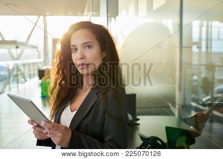 Confident mixed race entrepreneur in formalwear looking at camera while standing at spacious office lobby with panoramic windows and using digital tablet, waist-up portrait