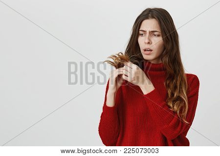 Horizontal portrait of young upset stunned woman in red sweater looking with sad expression of face at her dark long hair, being displeased with work of her hairdresser. Negative emotions and reaction