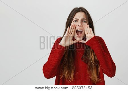 Horizontal portrait of cheerful dark-haired girl wearing red sweater keeping mouth wide opened, frowning face, calling for help. Shocked confused young cute female screaming in terror