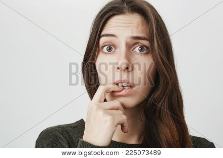 Close-up portrait of puzzled and confused woman with dark long hair dressed casually, looking at camera with puzzlement, thoughtful, not knowing what is wrong. Human feeling, emotions, face expressions