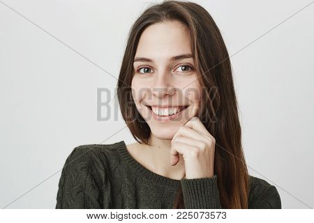Cheerful good-looking young woman in green sweater with dark hair smiling happily, receiving positive news. Attractive beautiful girl with looking at camera with joyful smile posing against studio wall