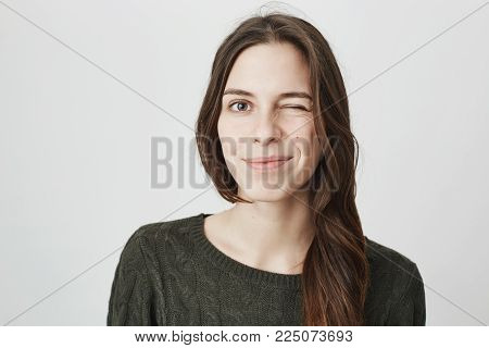 Close up picture of young pretty european girl in casual dark green sweater winking and smiling over white background. Mimic and expression concept. Woman says to her lover that everything is fine.