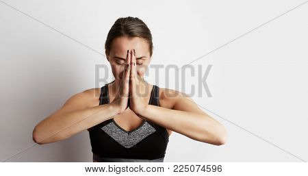 Woman practicing yoga, sitting in lotus position, hands together