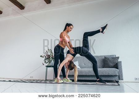 Fitness woman doing advanced bridge pose called one-legged wheel with assistance of instructor at home