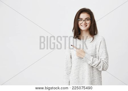 Studio portrait of young european model in glasses pointing left and smiling broadly. She suggests customer to discuss deal in office of company she works at. Maybe she can make her first sale. Advertisement concept