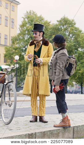 STOCKHOLM - SEPT 23, 2017: Elegant upper class gentleman with bicycle dressed in yellow overcoat and pants and a cylinder hat from aprox 1900 in the Bike in Tweed event September 23, 2017 in Stockholm, Sweden