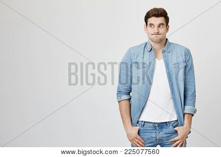 Studio shot of emotional clueless man with trendy haircut dressed in denim shirt over white t-shirt having confused puzzled look, pouting cheeks, shrugging shoulders as he doesn't know reason of accident