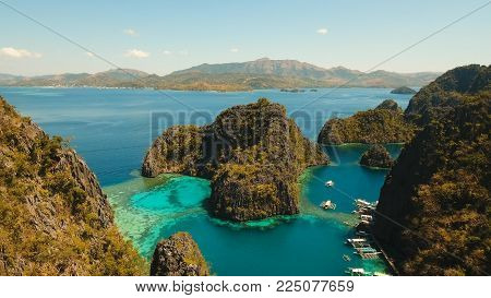 Tropical lagoon with azure water, beach by the Kayangan Lake, Philippines. Aerial view Coron island, with cove, bay at Kayangan lake. Lagoon with sailing boats. Aerial video. Philippines. Travel concept