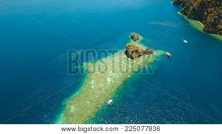 Aerial view: Lagoon with blue, azure water in the middle of small islands and rocks. Beach, tropical island, sea bay and lagoon, mountains with forest, Palawan, Coron. Busuanga. Seascape, tropical landscape. Philippines.
