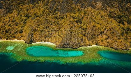 Aerial view: Lagoon with blue, azure water in the middle of small islands and rocks. Beach, tropical island, sea bay and lagoon, mountains with forest, Palawan, Coron. Busuanga. Seascape, tropical landscape. Philippines. Travel concept