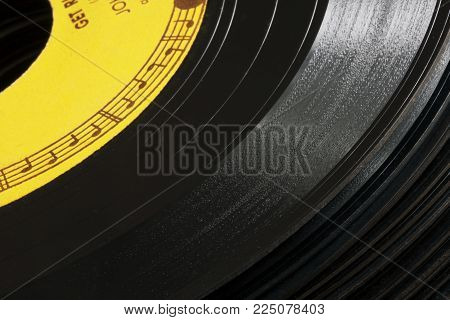 Musical notes encircle the center of an old 45 RPM record